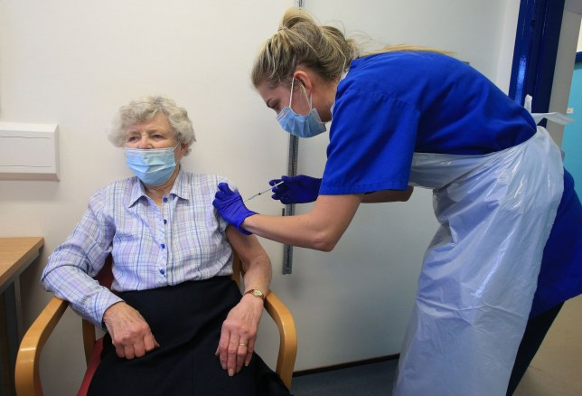 Nurse Practitioner Terri Welch (R) administers a dose of the Pfizer-BioNTech Covid-19 vaccine to a patient at the Haxby and Wigginton Group Medical Practice in Haxby, northern England on December 22, 2020. - Europe is expected to start a massive vaccination campaign after Christmas following the United States and Britain, which have begun giving jabs with an approved Pfizer-BioNTech shot, one of several leading candidates. (Photo by Lindsey Parnaby / AFP) (Photo by LINDSEY PARNABY/AFP via Getty Images)