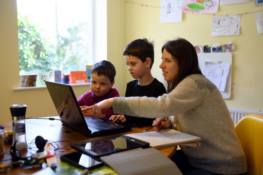Leo (C), aged 6, and Espen, aged 3, are assisted by their mother Moira as they navigate online learning resources provided by their infant school in the village of Marsden, near Huddersfield, northern England on March 23, 2020 on the first school day since the nationwide closure of almost all schools except for the children of 'key workers', amidst the novel coronavirus COVID-19 pandemic. - Families across the UK were coming to grips with homeschooling and online resources after the government closed schools to almost all children as a measure to combat the spread of the novel coronavirus. (Photo by OLI SCARFF / AFP) (Photo by OLI SCARFF/AFP via Getty Images)