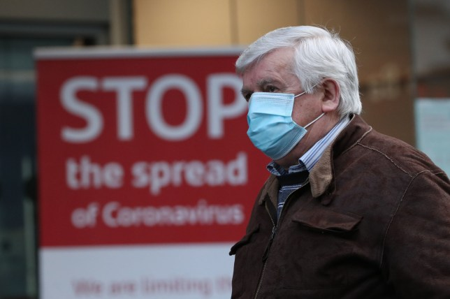 A man wearing a face mask walks past a coronavirus advice sign. It may become mandatory for people to wear masks in outside spaces.