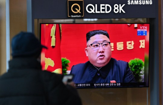 A man watches a television screen showing news footage of North Korean leader Kim Jong Un attending the 8th congress of the ruling Workers' Party held in Pyongyang,