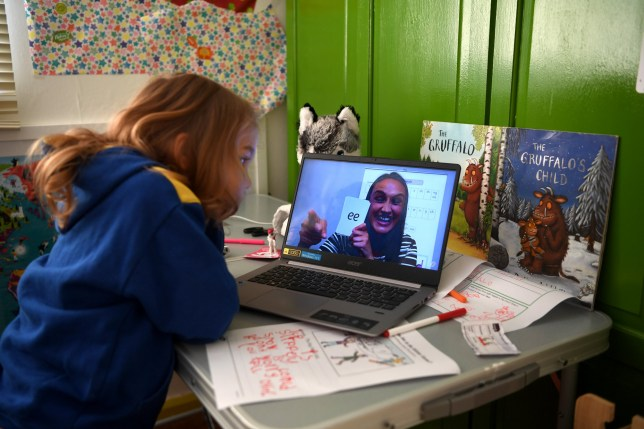 Five-year-old Lois Copley-Jones watches an online phonics lesson on a laptop in her bedroom on the second day of the nationwide school closures