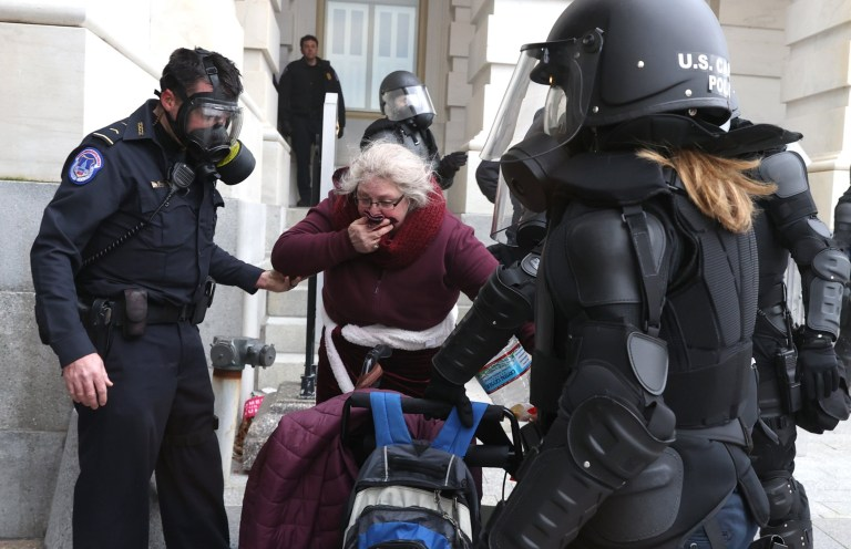 Capitol police officers help a woman as protesters gather on the U.S. Capitol Building on January 06, 2021 in Washington, DC.