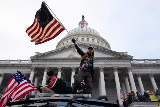 Trump-supporter waving an American flag on top of a car in front of the Capitol. Baked Alaska has been arrested by the FBI after storming the Capitol.