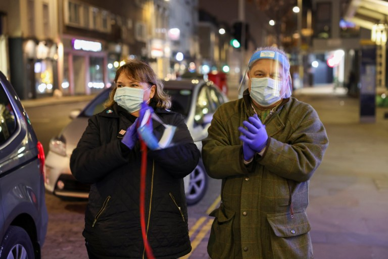 People wearing face masks take part in the Clap for Heroes campaign outside the Chelsea and Westminster Hospital following the outbreak of the coronavirus disease (COVID-19), in London, Britain, January 7, 2021.