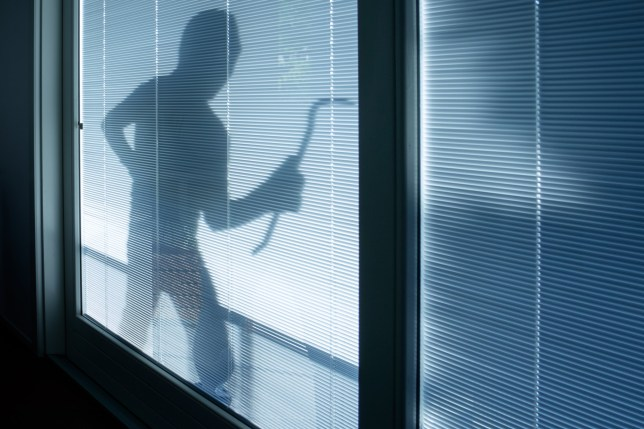 Silhouette of a burglar outside a house. Two burglars accidentally pocket-dialed Staffordshire Police and led them to their crime scene.