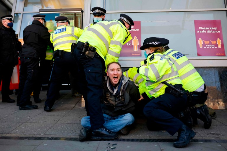 Police officers detain an anti-lockdown protester in Clapham, south London, on January 21, 2021 as life continues in Britain's third lockdown that prohibits large public gatherings in an effort to control surging cases of Covid-19. - Britain is under a renewed coronavirus lockdown to try to cut spiralling infection rates and deaths blamed on a fast-spreading virus variant. Stay-at-home restrictions, which involve closure of school for most children and all non-essential retail, allow for some forms of outdoor exercise once per day and are expected to last until at least mid-February. (Photo by Tolga Akmen / AFP) (Photo by TOLGA AKMEN/AFP via Getty Images)