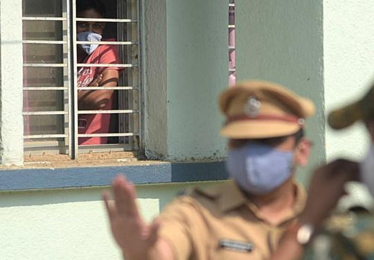 Un Indien regarde par une fenêtre alors que des policiers montent la garde devant l'hôpital général du district de Bhandara à la suite d'un incendie, à Bhandara, Maharashtra, Inde, le 9 janvier 2021. Au moins 10 nouveau-nés sont morts après qu'un incendie se soit déclaré sur l'enfant de l'hôpital unité de soins.  D'autres enquêtes sont en cours.