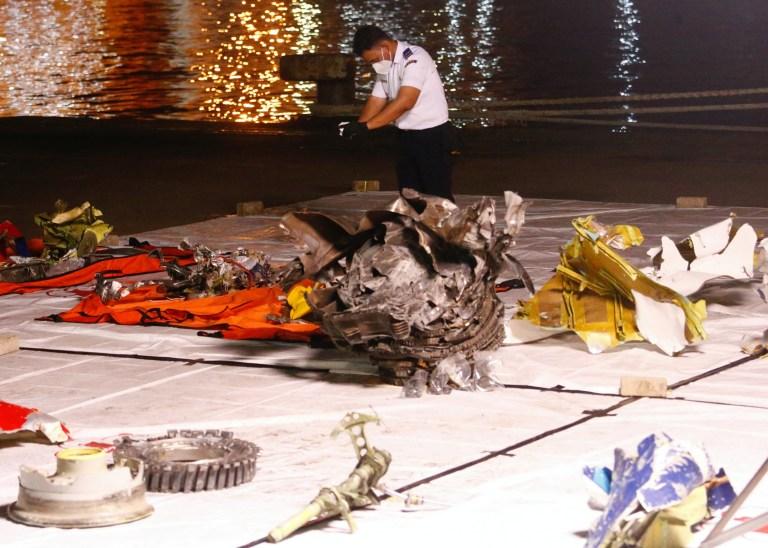 Un membre du Comité national de la sécurité des transports prend une photo des restes présumés du vol SJ 182 de Sriwijaya Air qui s'est écrasé en mer au large de la côte de Jakarta, au port de Jakarta International Container Terminal, en Indonésie, le 11 janvier 2021. REUTERS / Ajeng Dinar Ulfiana