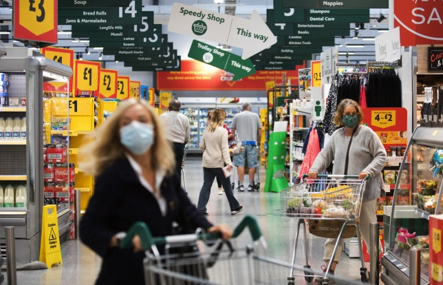 Customers wearing protective face masks pass along the main thoroughfare inside a Morrisons supermarket.