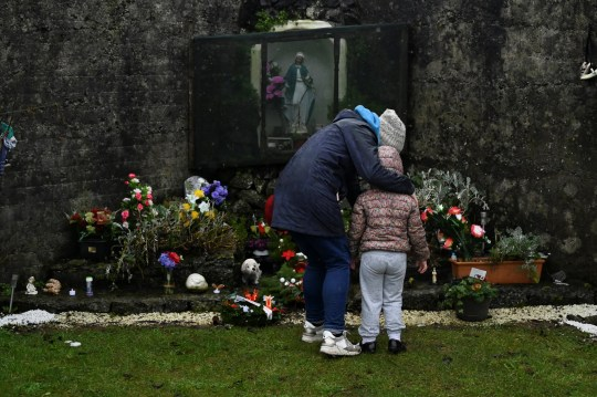 Denise Gormley and her daughter Rosa,7, pay their respects at the Tuam graveyard, where the bodies of 796 babies were uncovered at the site of a former Catholic home for unmarried mothers and their children, on the day a government-ordered inquiry into former Church-run homes for unmarried mothers is formally published, in Tuam, Ireland, January 12, 2021. REUTERS/Clodagh Kilcoyne