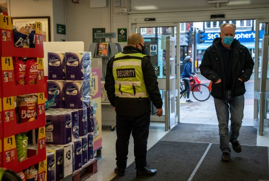 A security guard stands by the entrance to a Morrisons supermarket as a customer wearing a face mask enters the store on January 12, 2021 in London, United Kingdom.