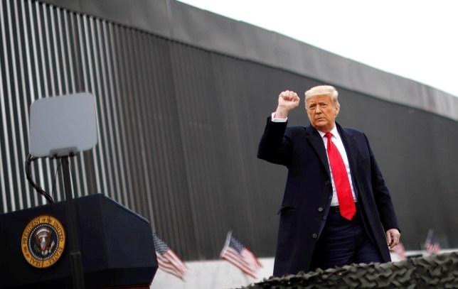U.S. President Donald Trump raises his fist as he visits the U.S.-Mexico border wall, in Alamo, Texas, U.S., January 12, 2021. REUTERS/Carlos Barria