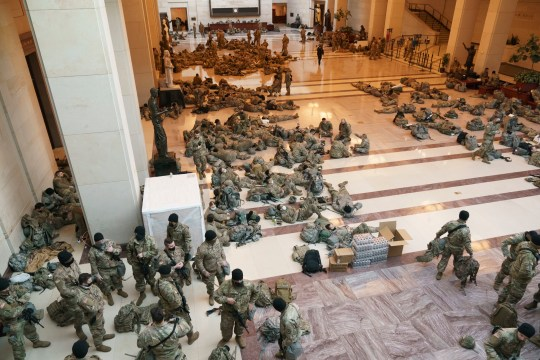 Hundreds of National Guard troops hold inside the Capitol Visitor's Center to reinforce security at the Capitol in Washington, Wednesday, Jan. 13, 2021. The House of Representatives is pursuing an article of impeachment against President Donald Trump for his role in inciting an angry mob to storm the Capitol last week. (AP Photo/J. Scott Applewhite)