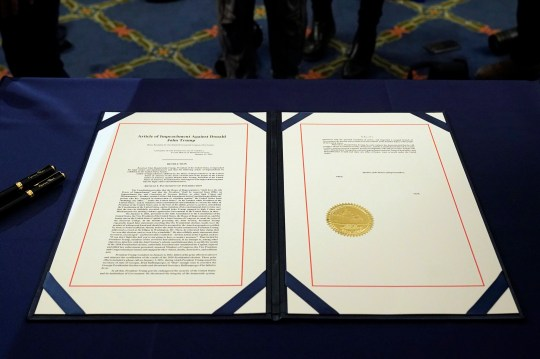 The article of impeachment against President Donald Trump on a table before House Speaker Nancy Pelosi of Calif., signs it in an engrossment ceremony before transmission to the Senate for trial on Capitol Hill, in Washington, Wednesday, Jan. 13, 2021. (AP Photo/Alex Brandon)