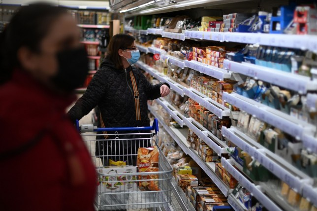 Shoppers wearing protective face coverings to combat the spread of the coronavirus, choose items in a Tesco supermarket in London on December 14, 2020. - With just over two weeks to go until Britain leaves the EU single market, preparations have been stepped up as fears grow about the impact of customs checks and congested ports. Concern is rising over the supply of perishable fresh fruit and vegetables, much of which is imported from EU countries. (Photo by DANIEL LEAL-OLIVAS / AFP) (Photo by DANIEL LEAL-OLIVAS/AFP via Getty Images)