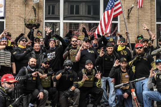 WASHINGTON, DC - DECEMBER 12: Members of the Proud Boys pose for a photo while flashing a gesture associated with the white power movement outside of Harry's bar during a protest on December 12, 2020 in Washington, DC. Thousands of protesters who refuse to accept that President-elect Joe Biden won the election are rallying ahead of the electoral college vote to make Trump's 306-to-232 loss official. (Photo by Stephanie Keith/Getty Images)