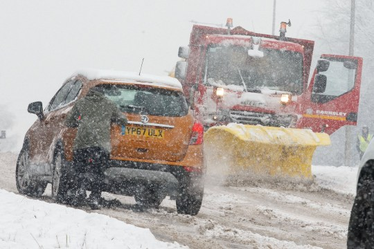 Snow hits the North of England causing travel chaos with snowfall set to last all day and fog expected to set in this evening. Pictured: A snow plough and grit spreader works to clear the roads as locals push cars up a hill in Barnsley, South Yorkshire. Jamie Lorriman mail@jamielorriman.co.uk www.jamielorriman.co.uk 07718 900288