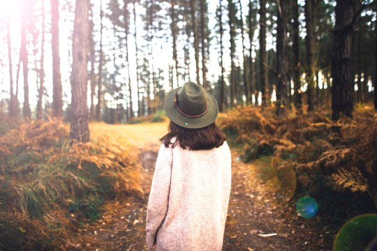 A young woman wearing a hat and walking by a beautiful forest area