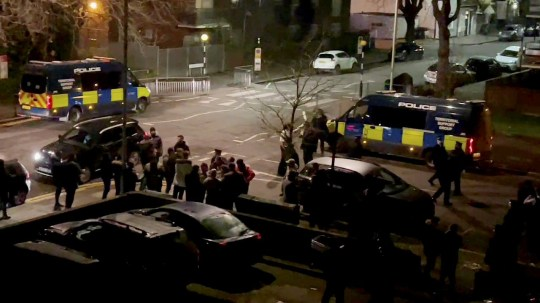 People and officers talking in between police vans. Police tried to disperse 'travellers' who allegedly flouted coronavirus rules and gathered for a wake at a caravan park in Seven Sisters, London.
