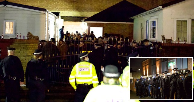 Police officers in masks talking to a large gathering of people through a gate. Police tried to disperse 'travellers' who allegedly flouted coronavirus rules and gathered for a wake at a caravan park in Seven Sisters, London.
