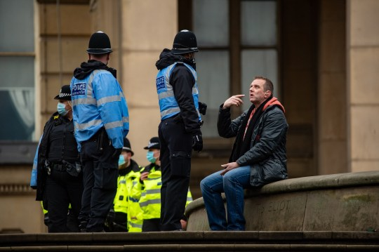 Police speak to a lone lockdown protester.  Brits have ignored Boris Johnson's pleas to stay at home this weekend.