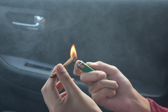 Hands lighting a joint. Brits are turning to a 'super weed' from California to help them get through dry January.