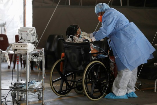 FILE PHOTO: Healthcare workers tend to a patient at a temporary ward set up during the coronavirus disease (COVID-19) outbreak, at Steve Biko Academic Hospital in Pretoria, South Africa, January 19, 2021. Phill Magakoe/Pool via REUTERS/File Photo