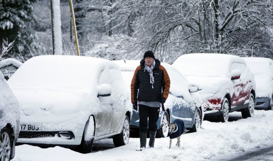 A man walks his dog through snow-covered roads in Allenheads, Northumberland. Picture date: Thursday January 21, 2021. PA Photo. Almost the whole of England, Wales and Northern Ireland are subject to yellow weather warnings for rain until Thursday morning, with a more serious amber warning stretching from the East Midlands to the Lake District. See PA story WEATHER Winter. Photo credit should read: Owen Humphreys/PA Wire