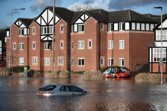 Residents of a care home are evacuated by members of a fire brigade after the river Weaver burst banks in Northwich, Britain, January 21, 2021. REUTERS/Molly Darlington