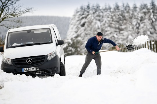 LAMANCHA, SCOTLAND - JANUARY 21: A man clears snow from around van which had become stuck in a snow drift on January 21, 2021 in Lamancha, Scotland. The first named storm of 2021 has swept across the North of England and Scotland, bringing flooding and heavy snow. (Photo by Jeff J Mitchell/Getty Images)