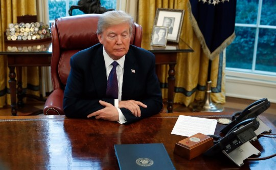 President Donald Trump sits at the Resolute Desk after signing Section 201 actions in the Oval Office of the White House in Washington