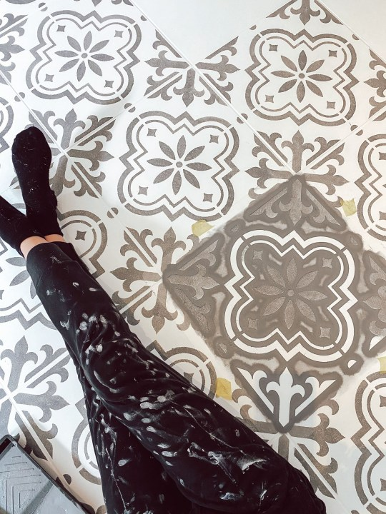 Rachel Marston painting her kitchen floor tiles with a stencil