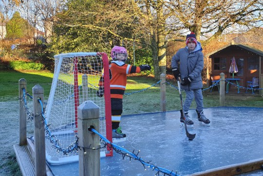 CRAIG MURDOCH / CATERS NEWS (PICTURED- Arran, 11, and five-year-old Anna play on the ice rink and practise thier ice hockey) -A hero dad has transformed his back garden into a magical ice rink for kids for under ??30. Craig Murdoch, 47, built the incredible winter paradise in just two days after new coronavirus restrictions shut sports facilities again. The rink has lasted up to two weeks and Craig and his family spend every day on it at the family home in Scotland. The cheap set up consists of scrap tinder and water, with the edge timbers costing ??15 and the heavy duty polythene sheet just ??12. - SEE CATERS COPY