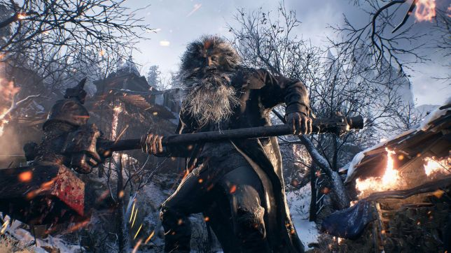 A screenshot from the video game Resident Evil Village with a man with a big grey beard carrying a huge bloody axe out in a snowy field surrounded by fire.