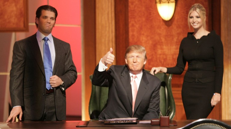 Donald Trump Jr, Donald Trump and Ivanka Trump behind a desk on The Apprentice
