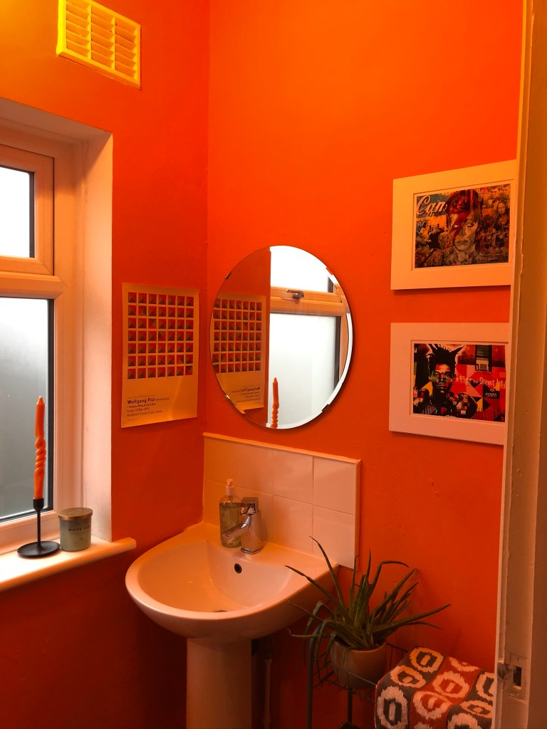 What I Rent: Iona and Jack, Oldham, Manchester - orange wall in bathroom with sink and circular mirror