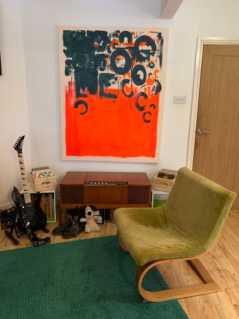 What I Rent: Iona and Jack, Oldham, Manchester - green chair in living room in front of large abstract painting