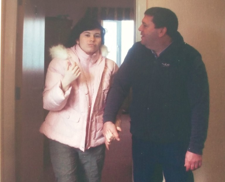 Sophie, wearing a pink coat and holding her dad's hand, as they leave a room.