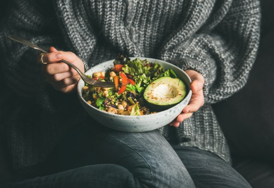 Healthy vegetarian dinner. Woman in grey jeans and sweater eating fresh salad, avocado half, grains, beans, roasted vegetables from Buddha bowl. Superfood, clean eating, dieting food concept (Credits: Getty Images/iStockphoto)