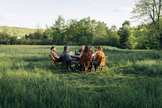 Group of friends enjoying dinner in rustic field