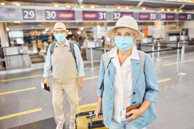 Two passengers in face masks and boarding passes standing at the airport