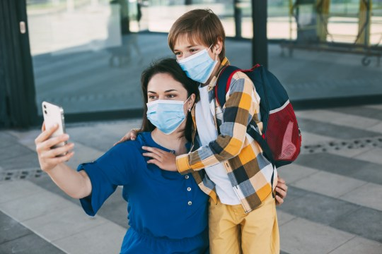 A mother and her son take a selfie wearing masks