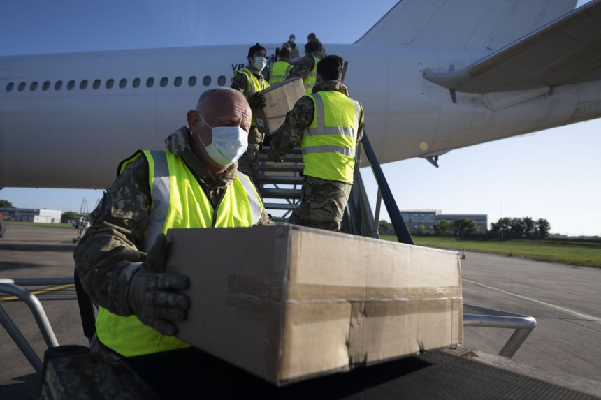 CARDIFF, WALES - MAY 12: The military help to unload boxes of PPE from a Nordwind Airlines passenger aircraft at Cardiff Airport on May 12, 2020, in Cardiff, Wales. The delivery, from Hanghzhou, China, contains 600,000 fluid resistant gowns and 1.2 million fluid resistant surgical masks. It is the third delivery of PPE to the airport since the end of April. (Photo by Matthew Horwood/Getty Images)
