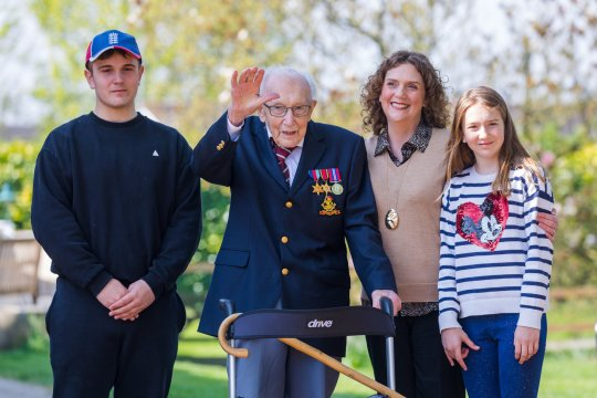 epa08981957 (FILE) - Then 99-year-old British veteran Captain Tom Moore (2-L) with grandson Benji (L), daughter Hannah Ingram-Moore (2-R) and granddaughter Georgia (R) outside his home after completing the 100th length of his back garden in Marston Moretaine, Bedfordshire, Britain, 16 April 2020 (reissued 02 February 2021). According to Moore's family, 100-year old Tom Moore, who raised about 33 million British pounds (almost 37 million euros) for Britain's National Health Service (NHS), has died. Moore was taken to a hospital 31 January 2021 after testing positive for Covid-19 and having problems with breathing. EPA/VICKIE FLORES *** Local Caption *** 56097687