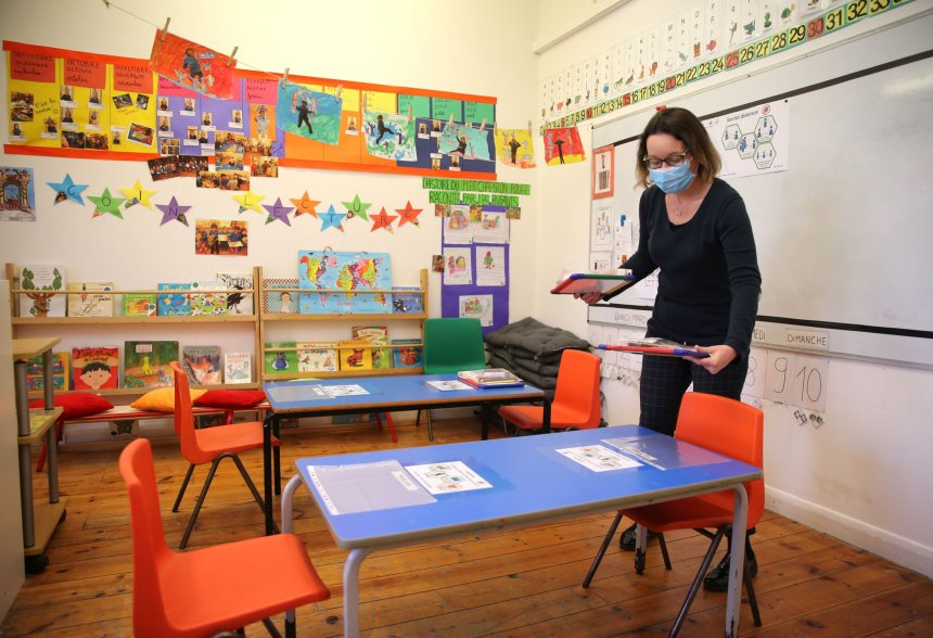 Head teacher Charlotte Beyazian places plastic bags containing materials on the tables for each pupil to help provide a teaching environment safe from Coronavirus for pupils and teachers at La Petite Ecole Bilingue at Kentish Town, north London, on May 20, 2020, ahead of the Government's proposed recommencing of education for Reception and Year 1 classes. (Photo by Isabel Infantes / AFP) (Photo by ISABEL INFANTES/AFP via Getty Images)