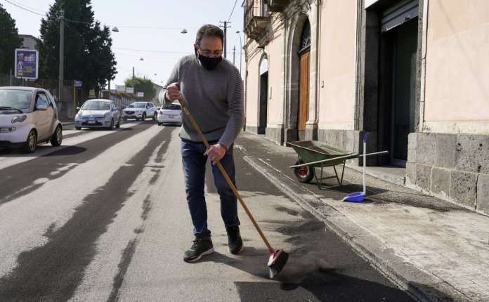 A person sweeps volcanic ashes from Mount Etna on a street in Giarre, Italy, February 28, 2021. REUTERS/Antonio Parrinello