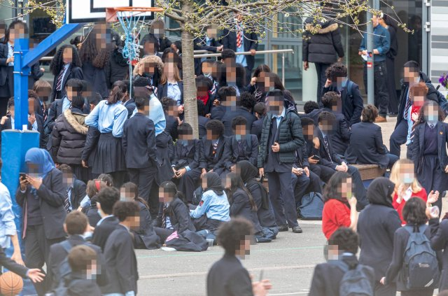 ? Licensed to London News Pictures. 31/03/2021. London, UK. School children at Pimlico Academy in London take part in a mass walk-out in protest over their school's new uniform policy, following claims it is discriminatory and racist. Photo credit: Alex Lentati/LNP *WARNING* PICTURE PIXELATED TO HIDE CHILDREN?S IDENTITIES. Pictures of Children in school playground*