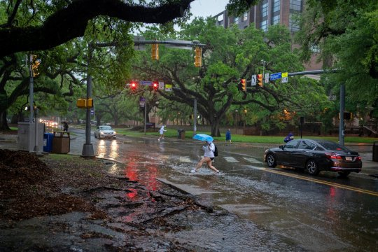 Students walk during a downpour on the Louisiana State University campus in Baton Rouge, Louisiana, the United States, April 13, 2021.