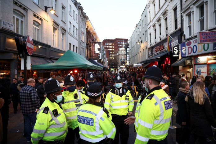 Police officers stand on the street next to people sitting on a bar terrace in Soho
