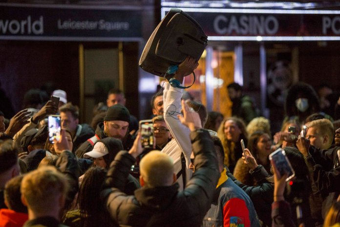 Members of the public dance to the music of a speaker in Leicester Square,